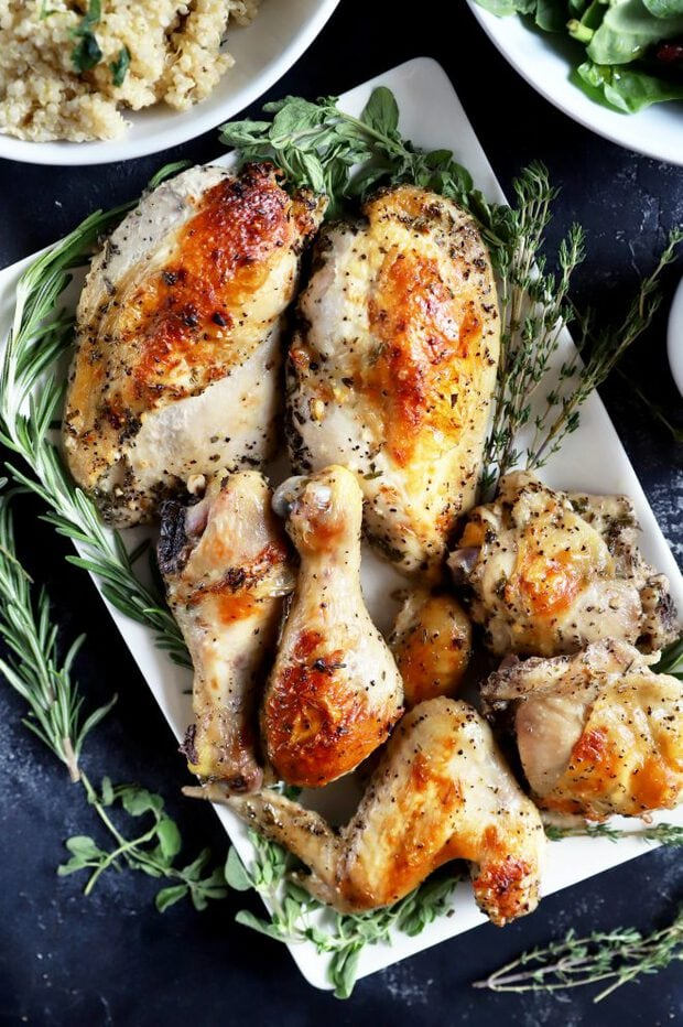 Roasted chicken on a white plate with fresh herbs