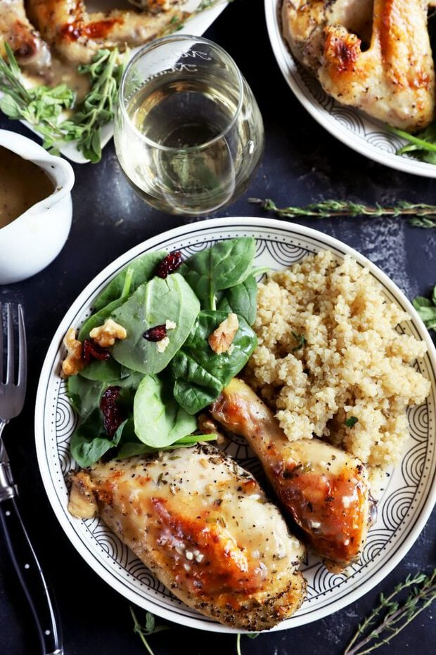 Roasted chicken on a plate with quinoa and salad