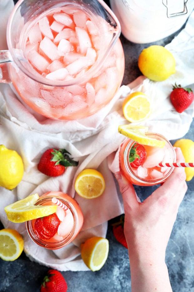 Hand holding jar of strawberry lemonade photo