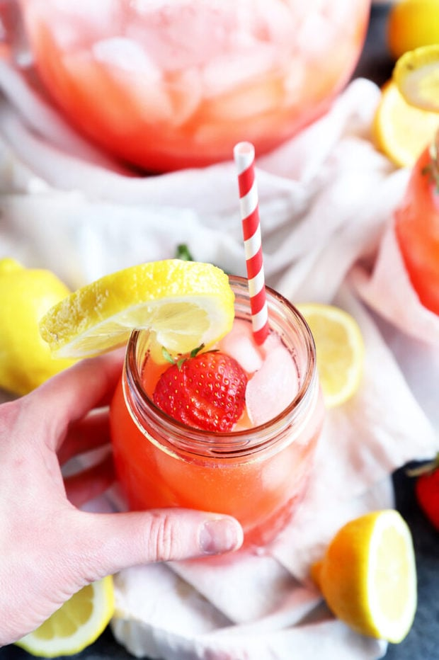 Image of hand holding vodka strawberry lemonade photo