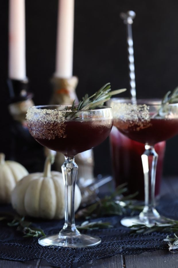 Spooky Pomegranate Mezcal Cocktail from the side with candlesticks