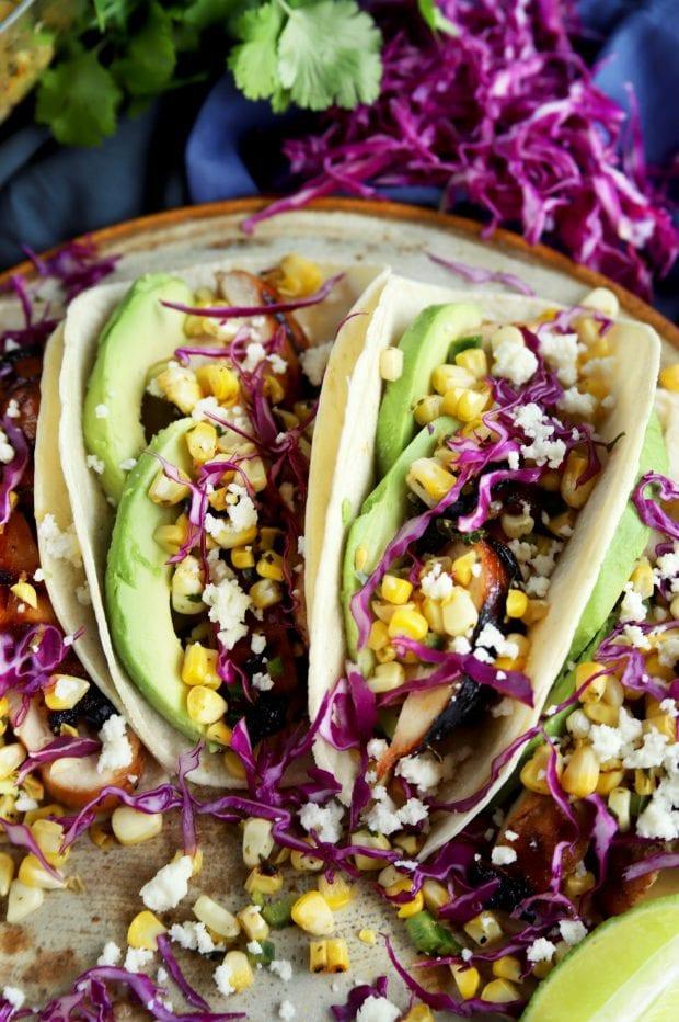 a couple Charred Corn Chicken Avocado Tacos