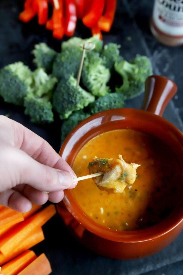 Bread piece being dipped into short rib fondue