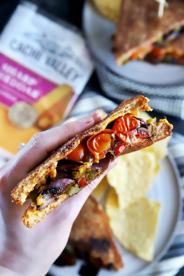 Holding half of a grilled cheese sandwich with grilled vegetables