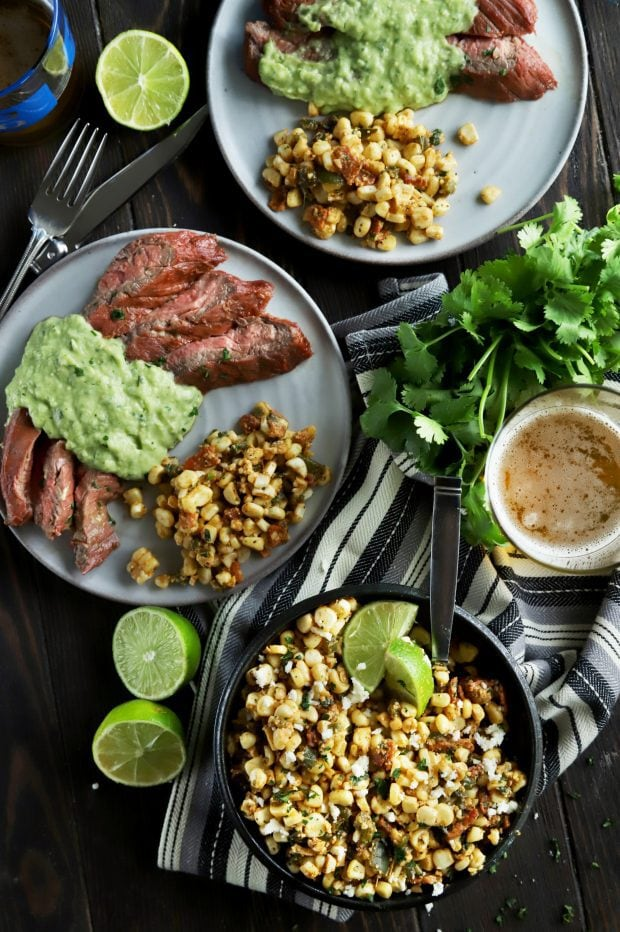 A spread of grilled corn salad with steak and limes
