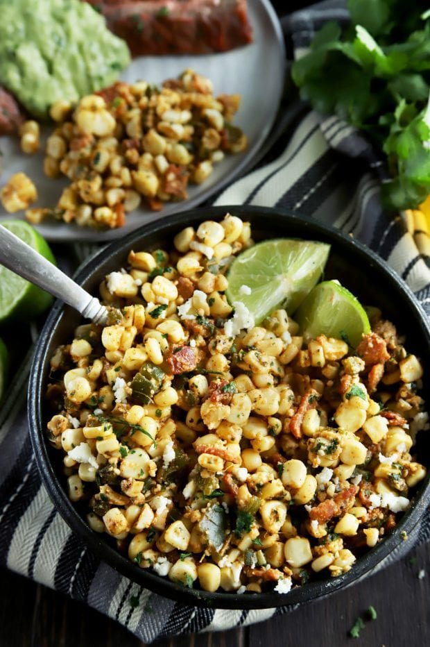 Grilled corn salad in a bowl with limes