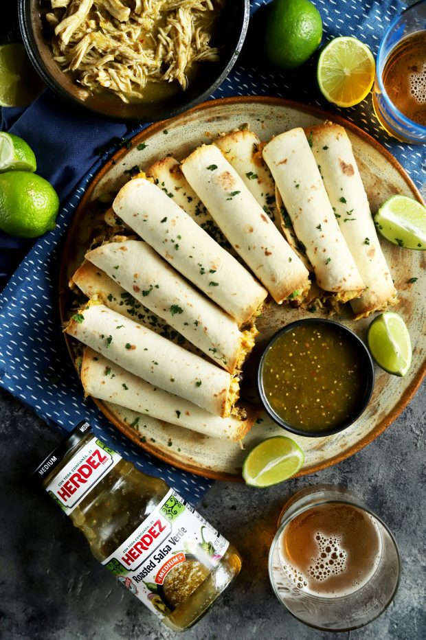 A pile of baked taquitos for a party with a beer and jar of salsa verde