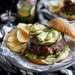 Burger with pickles, avocado, and chips