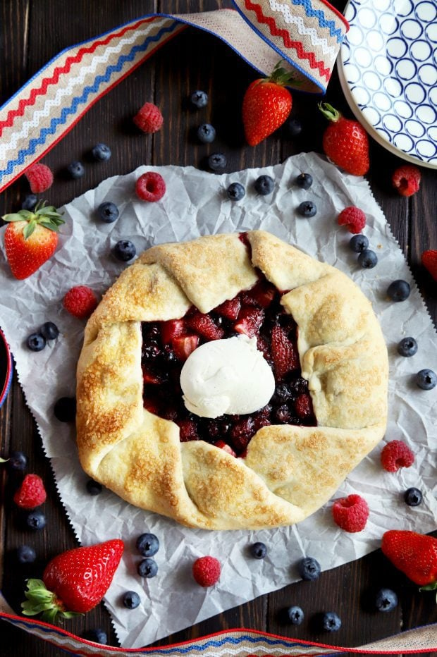 A red white and blue galette with berries on parchment paper