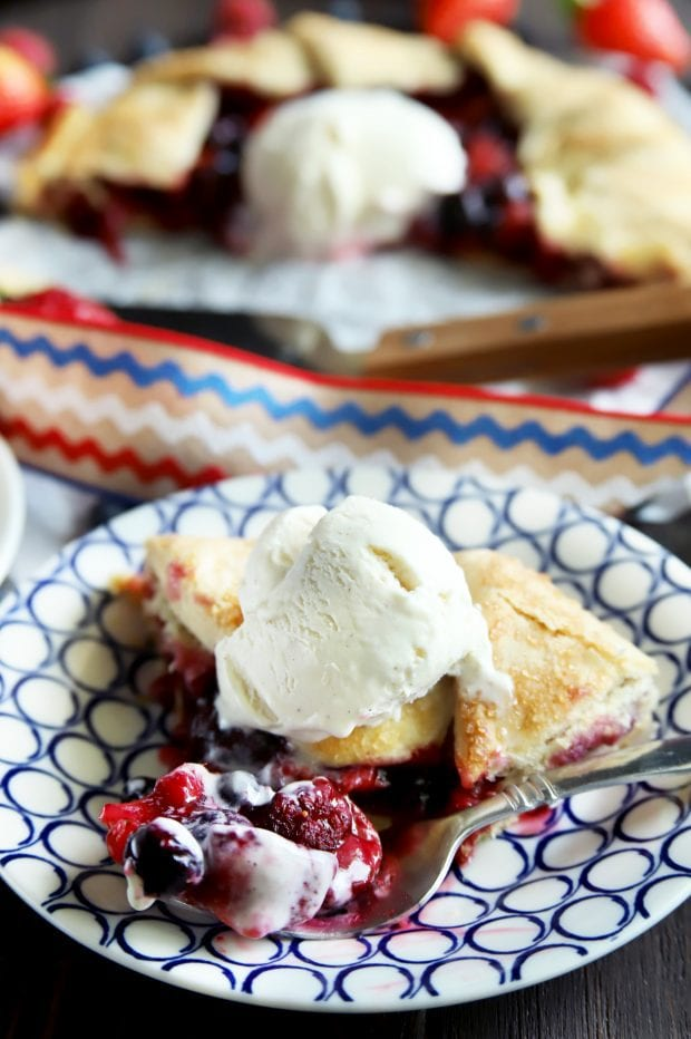 Triple berry galette piece with a fork taking a bite