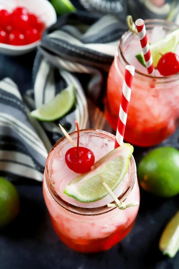 Overhead shot of summer cocktails with cherries and lime