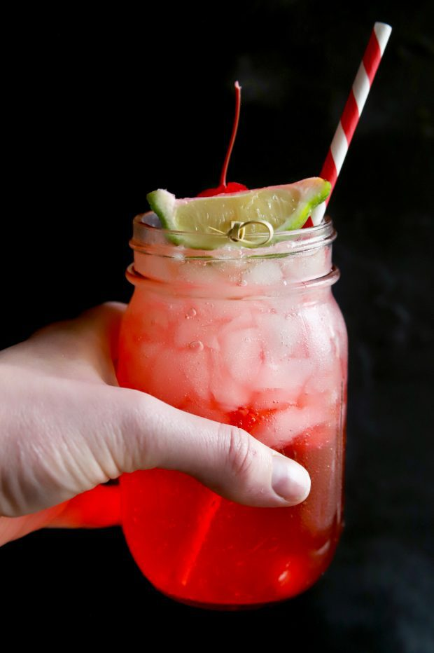 Holding a bubbly cherry and lime cocktail in a mason jar