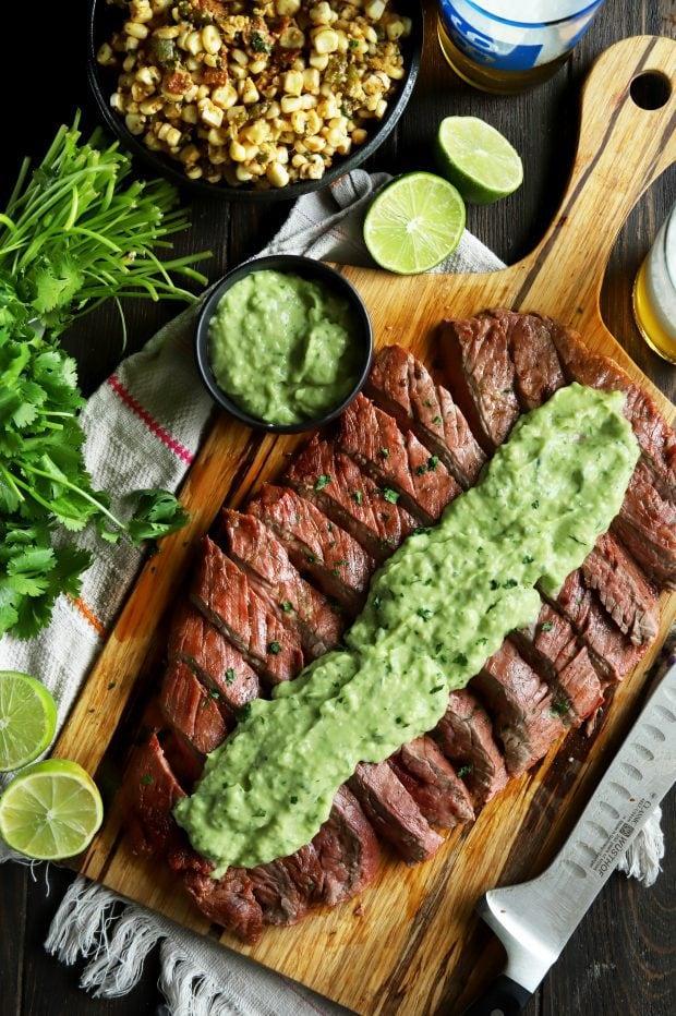Sliced flank steak with creamy avocado salsa on top