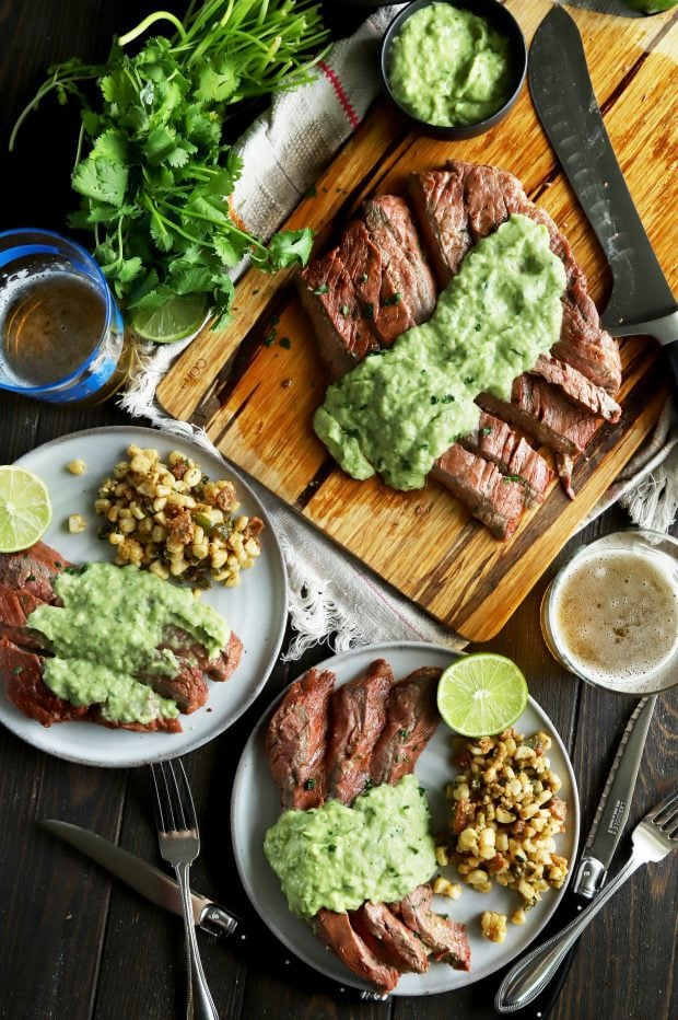 Overhead shot of steak, corn salad, and creamy avocado salsa