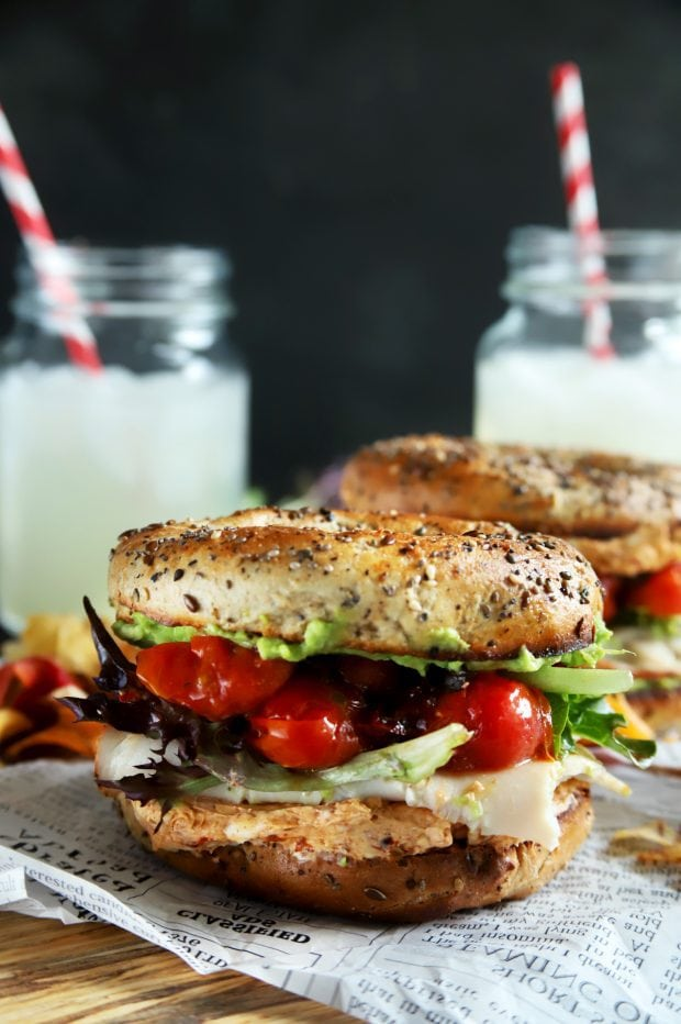 Healthy turkey bagel sandwich with avocado and tomatoes