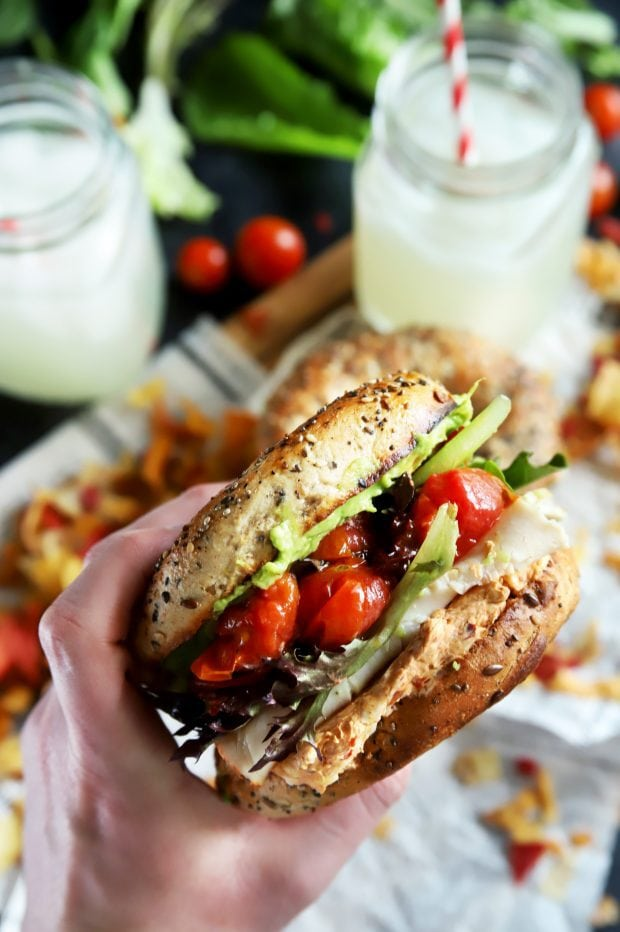 Hand holding a bagel sandwich with turkey and vegetables