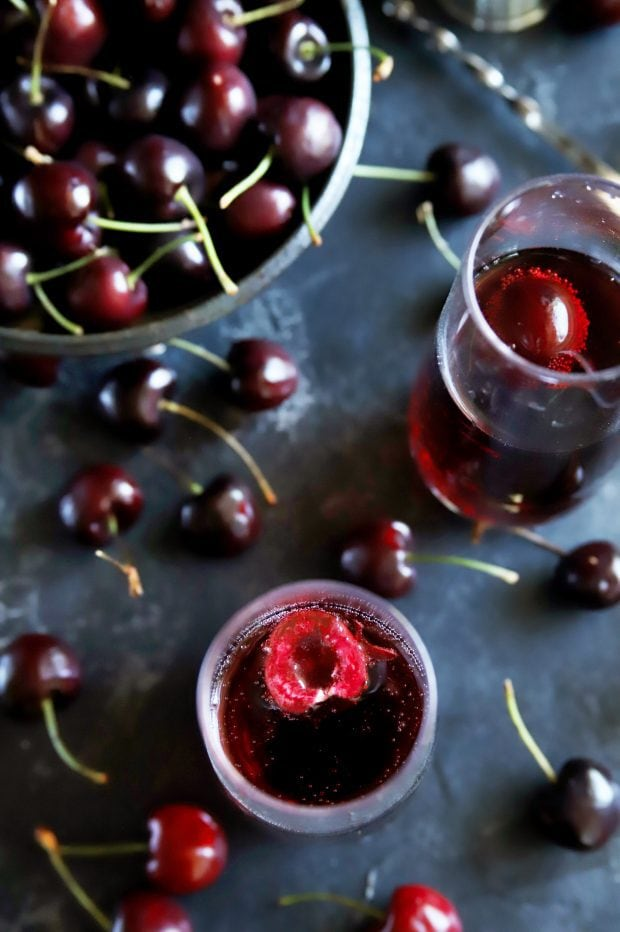 Fresh cherries in a bowl around mimosas in champagne flutes