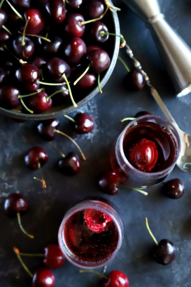 Fresh cherries with jigger, champagne glasses and mimosa cocktails