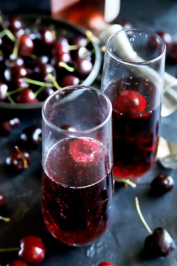 Side shot of champagne flutes with cherry rose mimosas and fresh cherries