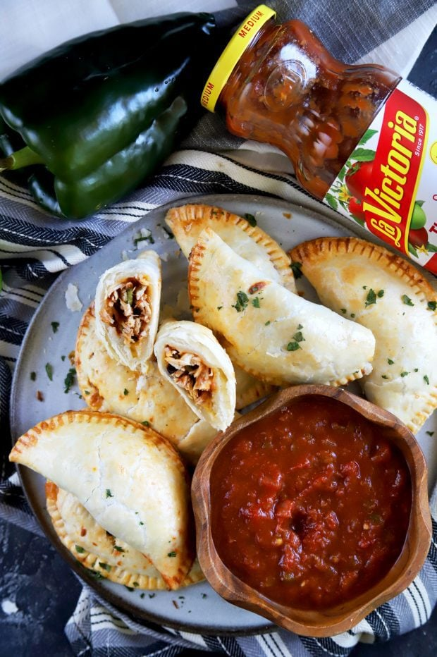 Lots of empanadas with one cut in half and with salsa