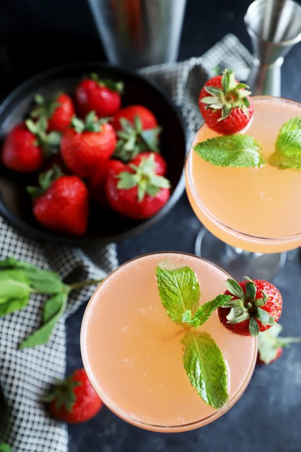 Berries and herbs with vodka for a cocktail in coupe glasses
