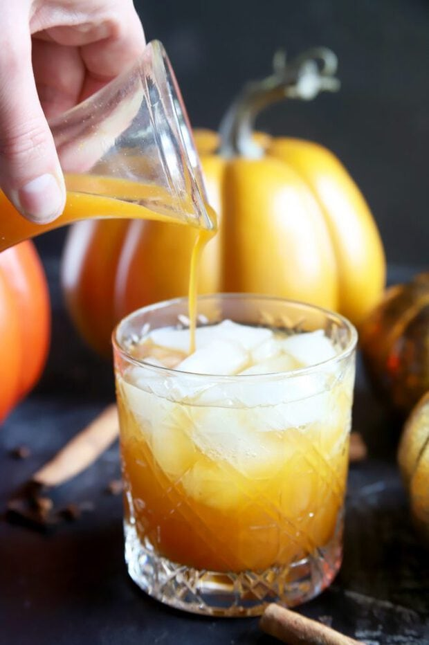 Pouring simple syrup into a pumpkin cocktail