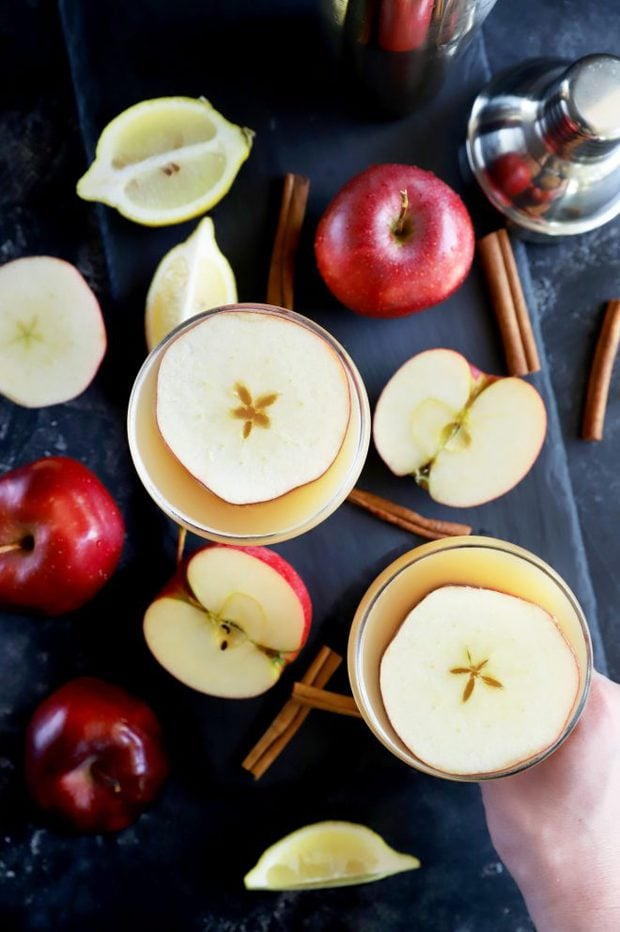 Overhead photo of whiskey apple cocktails with apples