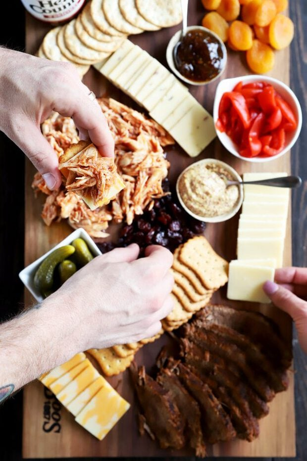 Hands in for BBQ meat, cheese, and crackers