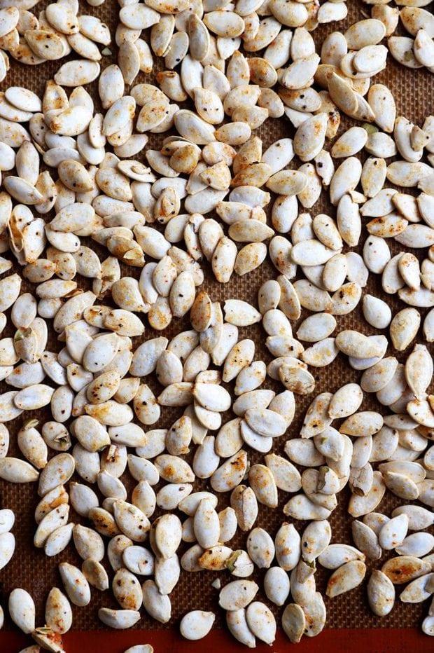 Overhead photo of pumpkin seeds on a baking sheet