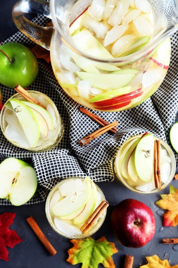 Overhead photo of apple pie sangria in cups and a pitcher