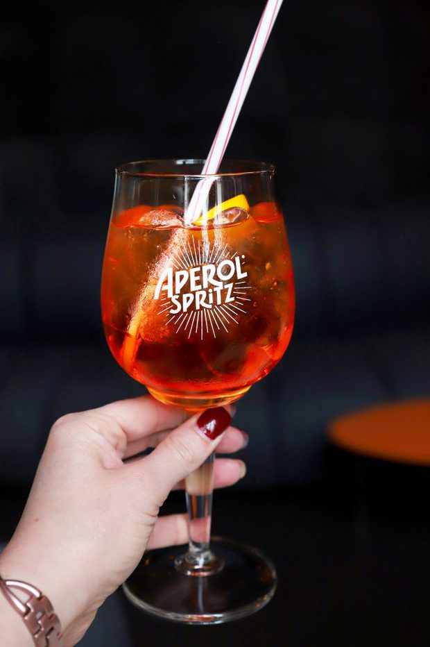 Hand holding an Aperol Spritz for a guide to Milan