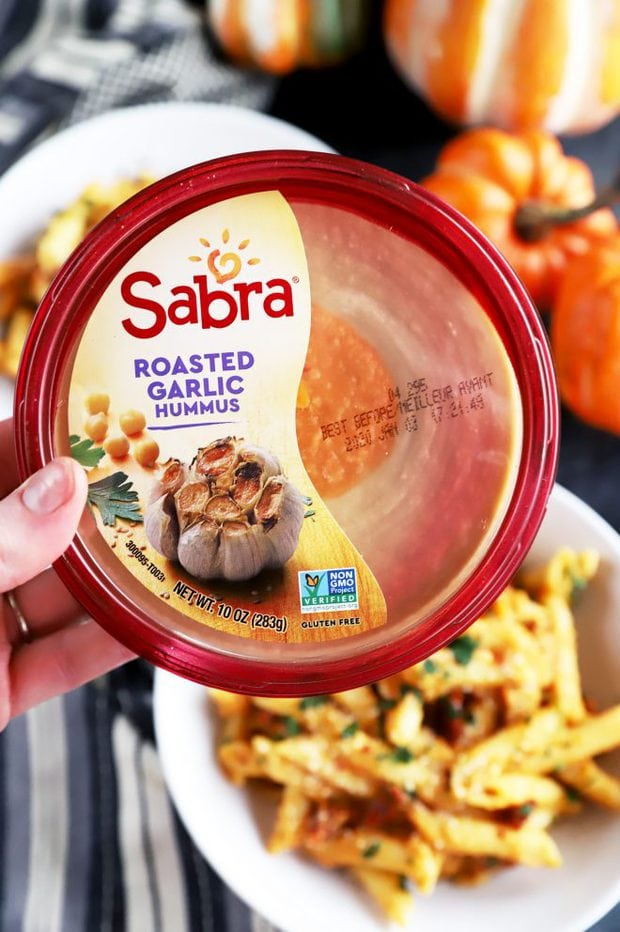 Hand holding a tub of Sabra Roasted Garlic Hummus