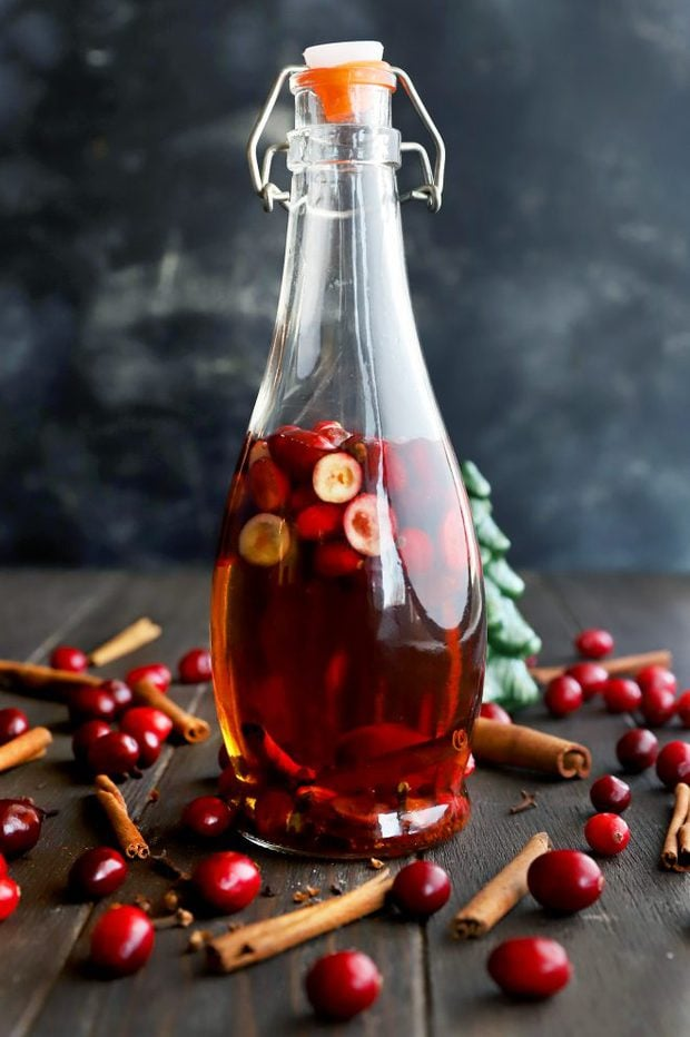 Image of infused whiskey in a bottle with cranberries and cinnamon