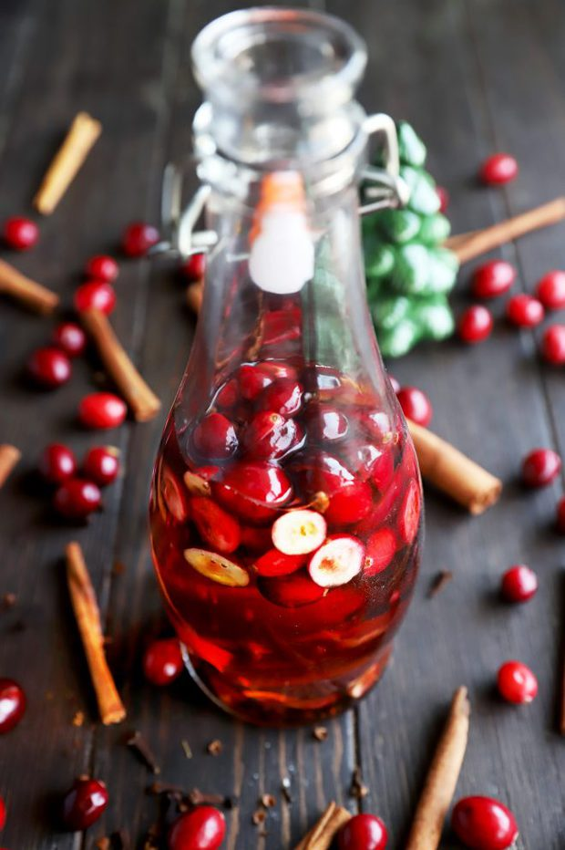 Whiskey in a bottle with cranberries and cinnamon