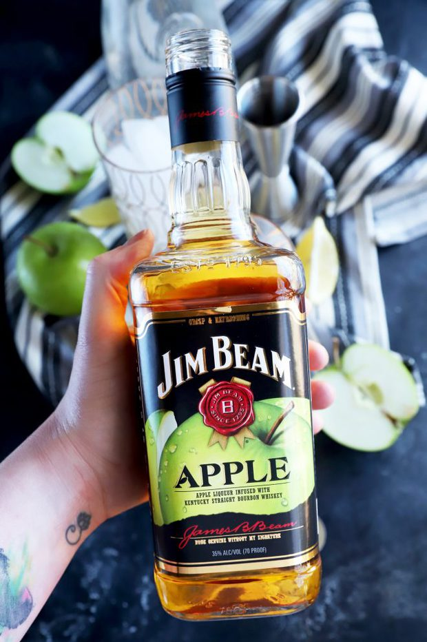 Photo of hand holding Jim Bean Apple bottle
