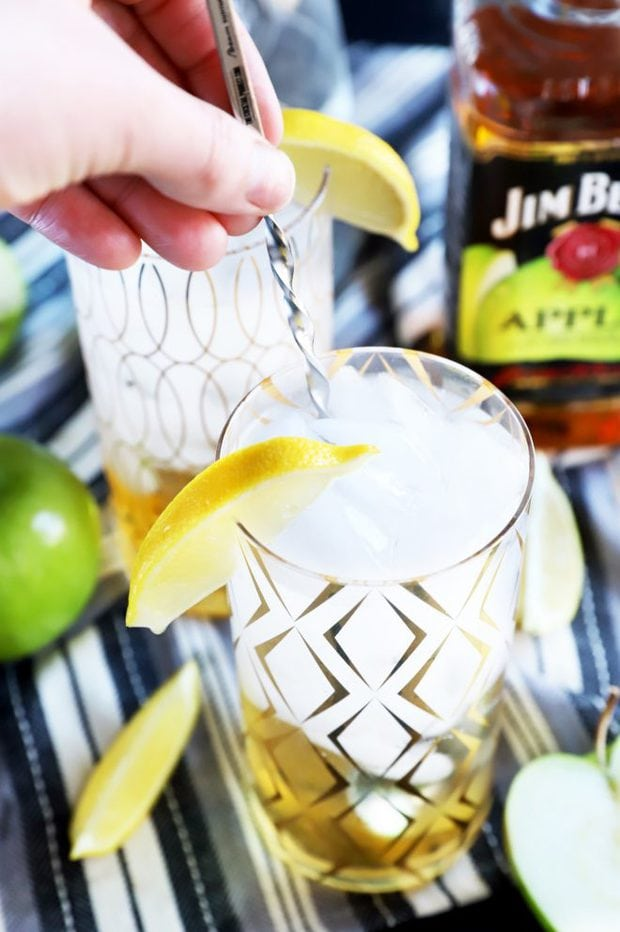 Hand stirring a cocktail in a glass photo