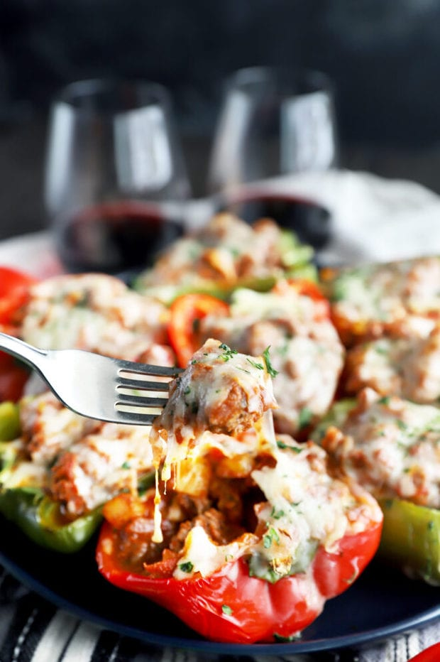 Fork of cheesy stuffed peppers on a plate image