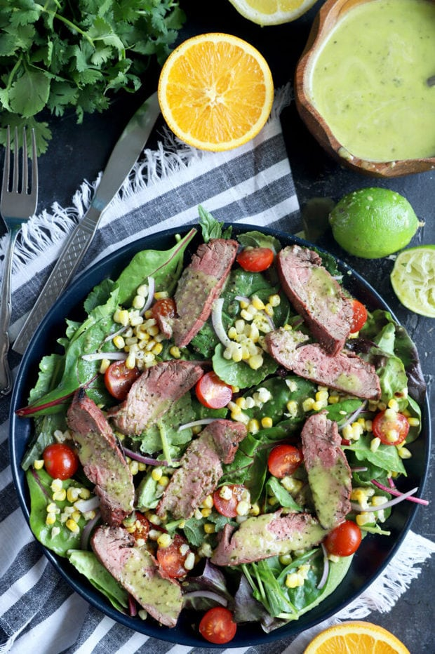 Photo of mojo steak on greens with corn