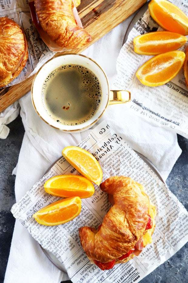 Overhead photo of breakfast sandwich with oranges and coffee