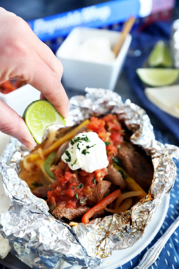 Squeezing a lime over steak fajitas image