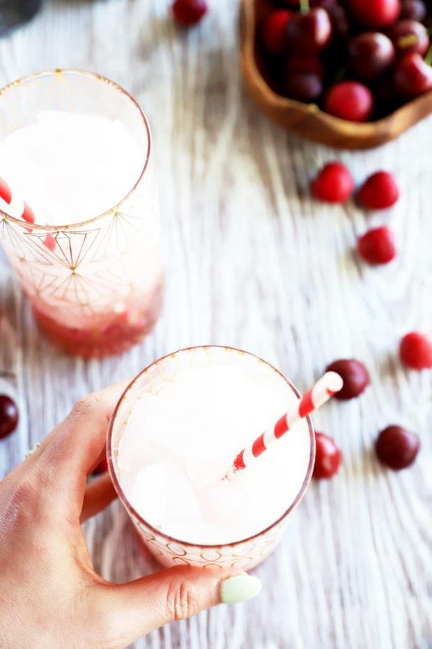 Hand holding cherry soda in glass