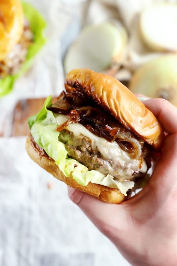 Hand holding french onion burger