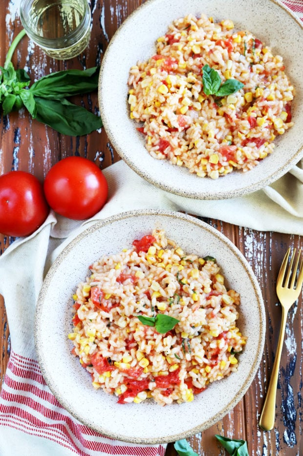 Summer tomato corn risotto in bowls with basil photo