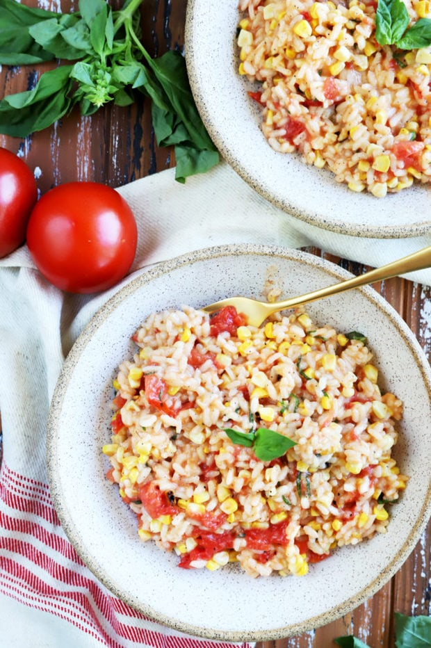 Photo of risotto in bowls with tomatoes and corn